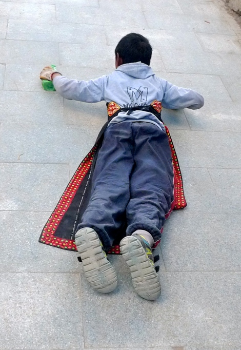 Look at the young boy, he is so determined to do prostration.